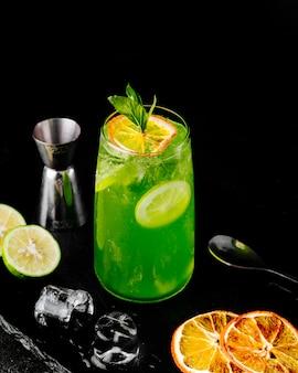 Limonade verte fraîche avec du jus de citron orange et des tranches à la menthe.