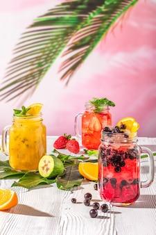 Limonades de fruits d'été sur une table en bois blanche dans un bocal à conserves