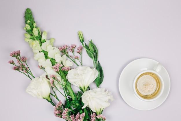 Le limonium; bouquet de fleurs eustoma et snapdragons près de la tasse à café sur fond blanc