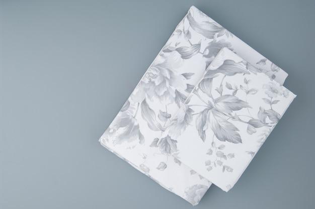 Linge de lit neuf plié avec motifs sur fond gris, vue de dessus