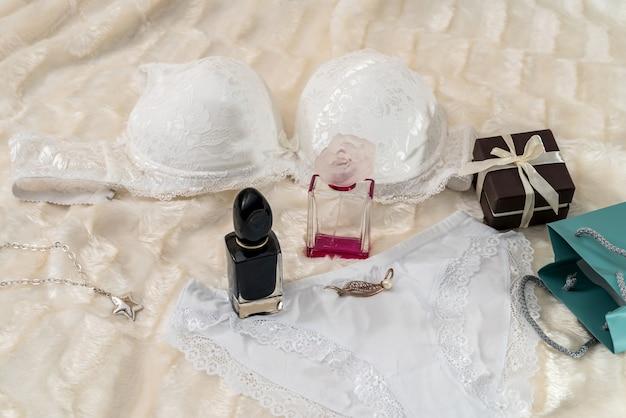 Lingerie blanche séduisante avec boîte-cadeau sur tissu beige