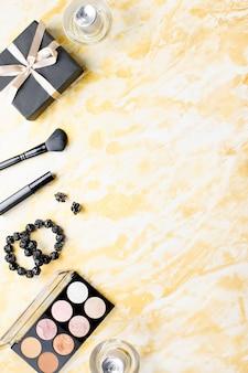 Lingerie en dentelle noire avec des produits de beauté, maquillage cosmétique, bijoux en noir et or. mise à plat de la mode, vue de dessus