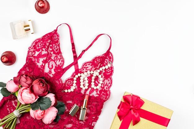 Lingerie en dentelle rouge femme avec coffret, fleurs, maquillage articles sur fond blanc. carte postale pour la journée de la femme.