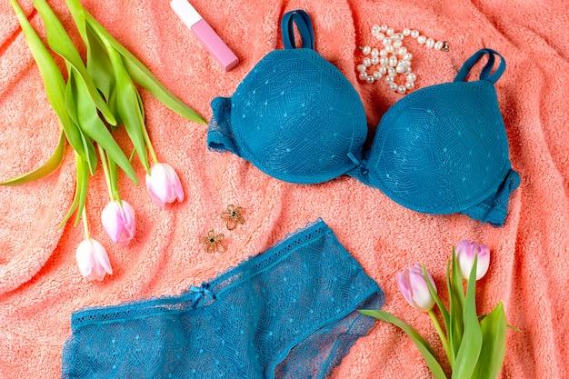 Lingerie en dentelle sur la table de lit avec des fleurs et des bijoux, vue de dessus, espace copie