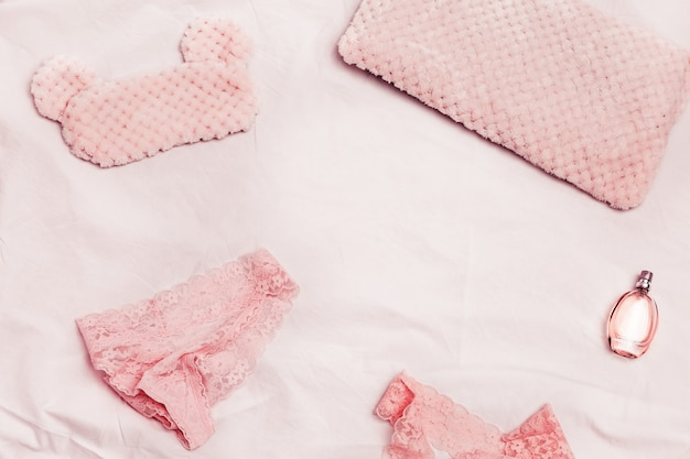 Lingerie féminine à la mode et parfum, culotte et soutien-gorge en dentelle pour femme, oreiller et masque pour les yeux moelleux pour dormir sur un drap blanc. vue d'en-haut.