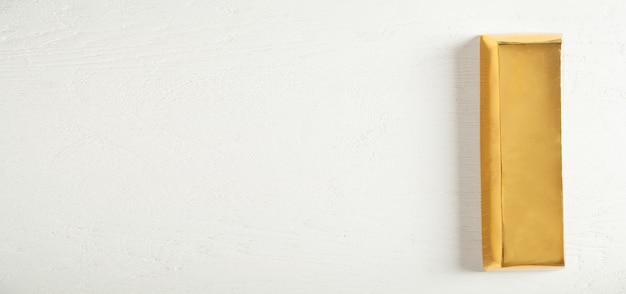 Lingot d'or sur le bureau blanc. espace pour votre texte
