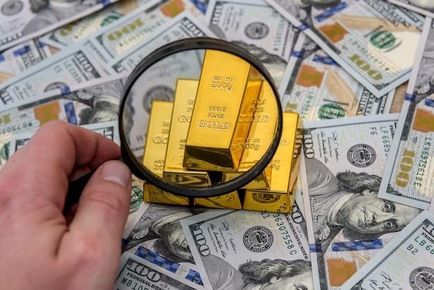Lingot, or ou lingot sur billet en dollars américains avec loupe