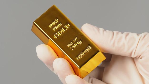 Lingot d'or à la main et portez un gant en latex isolé sur fond gris.