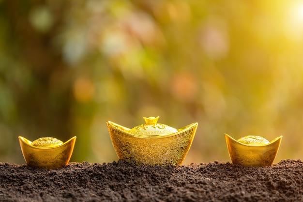 Lingot d'or pour la décoration du nouvel an chinois sur le dessus de la pile de sol en arrière-plan flou de jardin
