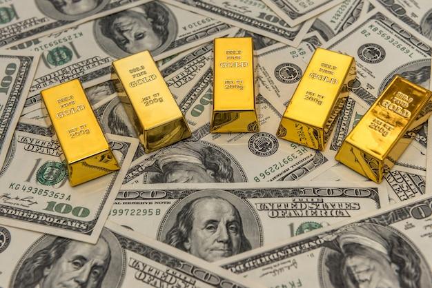 Lingots d'or sur le billet de 100 dollars usd en arrière-plan. concept de finances et d'épargne.
