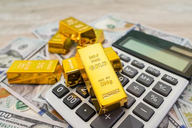 Lingots d'or avec calculatrice et dollars