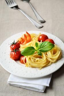 Linguini servi avec tomates cerises grillées et crevettes sur fond de lin beige