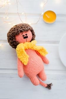 Lion orange jouet tricoté avec écharpe jaune sur table en bois blanc