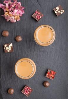 Liqueur de chocolat sucré en verre avec des bonbons au chocolat sur une ardoise en pierre noire. vue de dessus, espace copie.