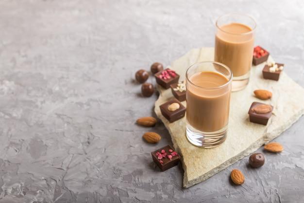 Liqueur de chocolat sucré en verre et pierre ardoise. vue de côté.