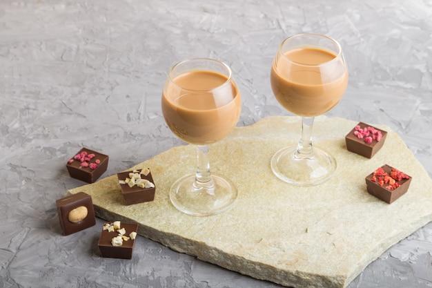 Liqueur de chocolat sucré en verre sur une surface en béton gris et ardoise en pierre. vue de côté.