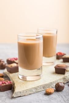 Liqueur de chocolat sucré en verre sur une surface en béton gris et ardoise en pierre. vue latérale, mise au point sélective.