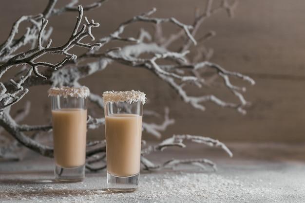 Liqueur de crème irlandaise ou liqueur de café avec une couronne de flocons de noix de coco sur un verre court. décorations de noël hivernales