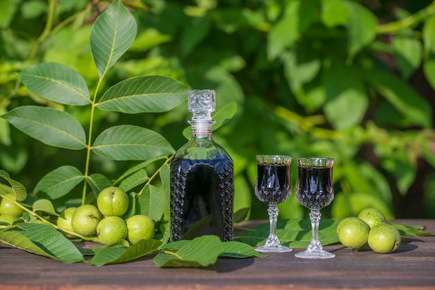 Liqueur de jeunes noix vertes, remède contre les maux d'estomac, gros plan. teinture de noix vertes dans une bouteille en verre sur une table dans le jardin