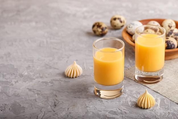 Liqueur d'œufs sucrée en verre avec œufs de caille et meringues