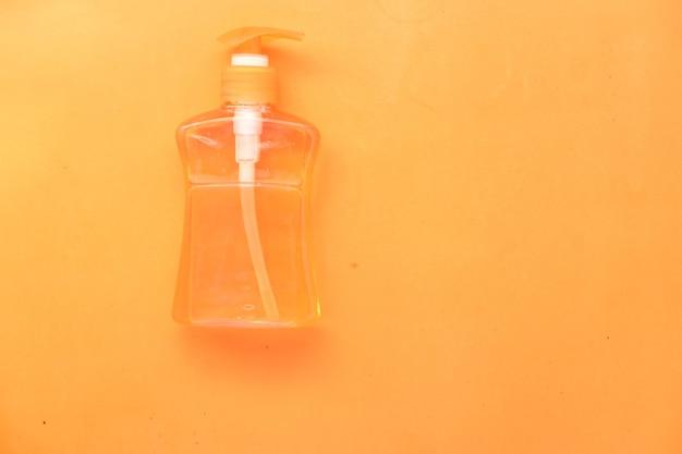 Liquide de lavage des mains dans un récipient sur fond orange