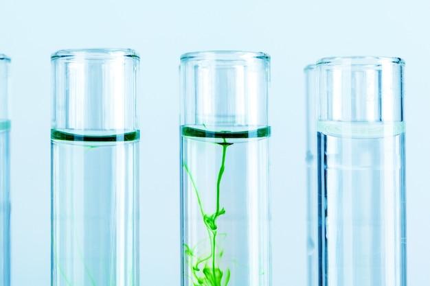 Liquides verts dans des éprouvettes en laboratoire chimique se bouchent