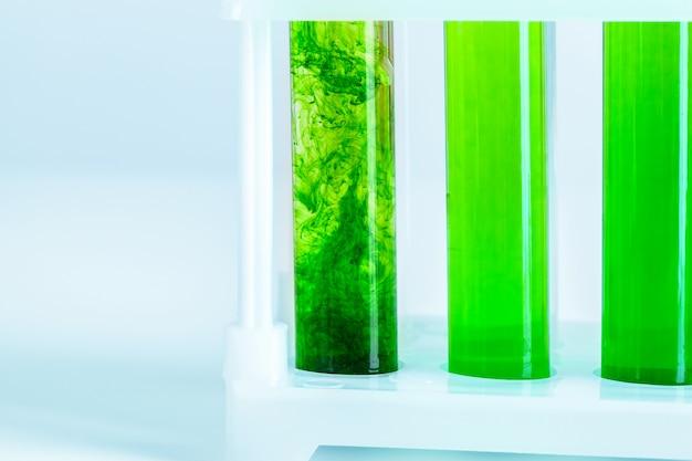 Liquides verts dans des tubes à essai en laboratoire de chimie se bouchent