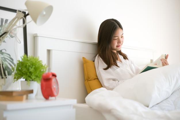 Lire une belle femme au lit le matin.