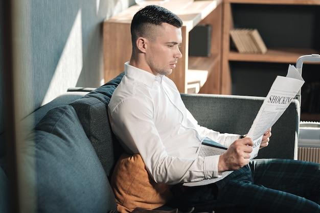 Lire le journal. jeune bel homme d'affaires assis sur le canapé en lisant le journal le matin