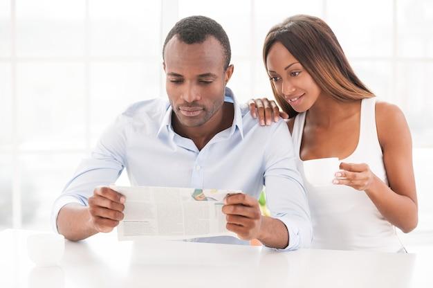 Lire un nouveau journal ensemble. beau jeune couple africain assis l'un près de l'autre et lisant le journal tandis qu'une femme tenant une tasse de café et souriant