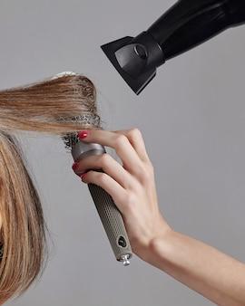 Lissage des cheveux en gros plan avec un sèche-cheveux