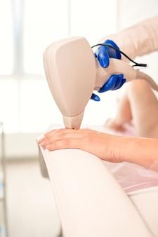 Lisser les doigts de la main de la femme pendant l'épilation au laser sur fond de bureau de cosmétologues