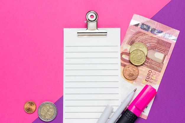 Liste de contrôle avec des billets en euros, des pièces de monnaie, un stylo et un marqueur sur un fond rose et violet. vue de dessus