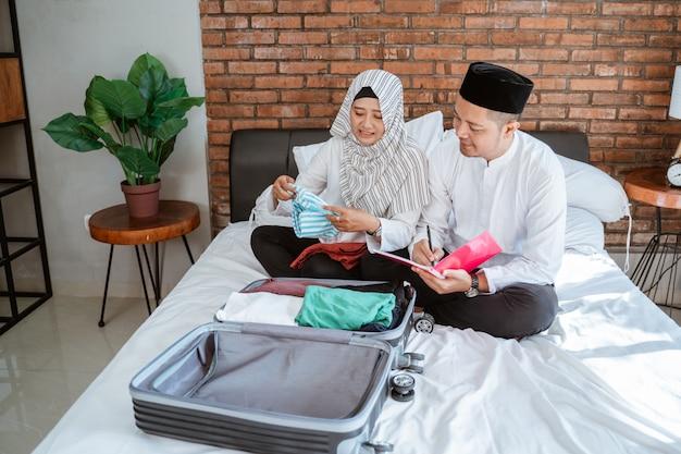 Liste de contrôle de couple leurs affaires sur une valise