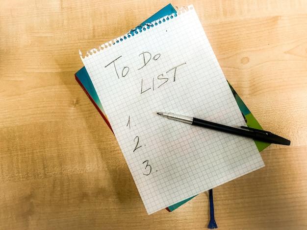 Liste de contrôle à faire à la main écrite sur du papier bloc-notes posée sur une table en bois. stylo plume posé dessus. photo de haute qualité