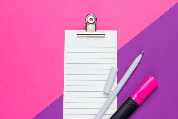 Liste de contrôle vide avec stylo et marqueur sur fond rose et violet. vue de dessus