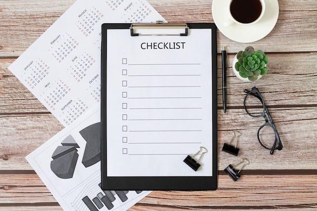 Liste de contrôle vierge sur un bureau en bois avec café, verres, calendrier, plantes. vue de dessus du concept d'entreprise