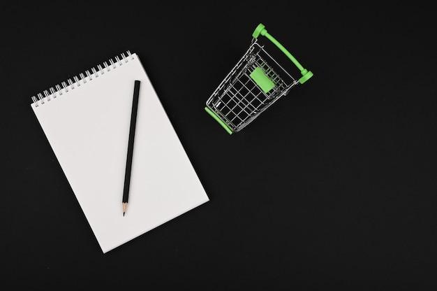 Liste de courses. cahier et crayon sur fond noir. panier avec copie espace