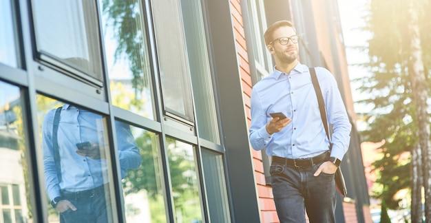 Liste de lecture préférée jeune homme d'affaires heureux écoutant de la musique avec des écouteurs sans fil et un mobile