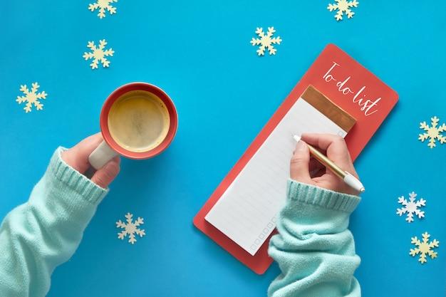 Liste de noël et mains de femme en pull couleur menthe avec tasse de café sur la table bleue
