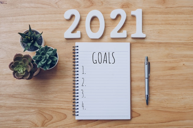 Liste des objectifs du nouvel an 2021. table de bureau avec cahiers et pancil avec plante en pot.
