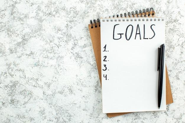 Liste d'objectifs vue de dessus écrite sur bloc-notes stylo noir sur fond gris avec lieu de copie