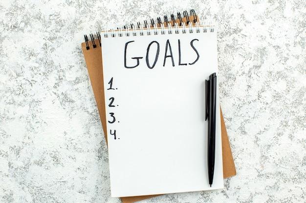 Liste d'objectifs vue de dessus écrite sur un stylo noir pour ordinateur portable sur fond gris