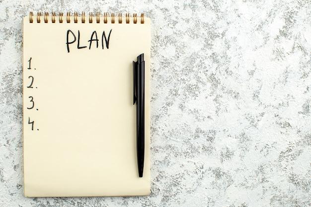 Liste de plans vue de dessus écrite sur un stylo noir pour ordinateur portable sur fond gris blanc copie lieu