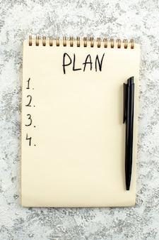 Liste des plans vue de dessus écrite sur un stylo noir pour ordinateur portable sur fond gris blanc