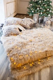 Le lit au décor du nouvel an se dresse sur fond d'arbre de noël décoré. décoration festive dans la maison avec des guirlandes jaunes