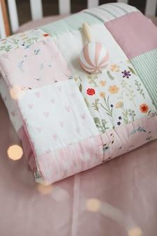 Lit bébé avec couverture patchwork rose et textile pour chambre d'enfant