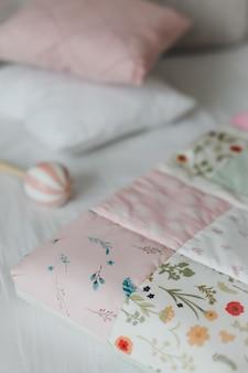 Lit bébé douillet avec couverture patchwork rose