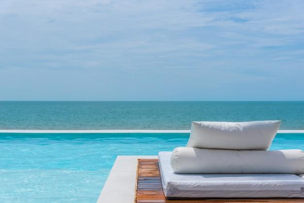 Lit blanc au bord de la piscine la mer avec le ciel de l'horizon