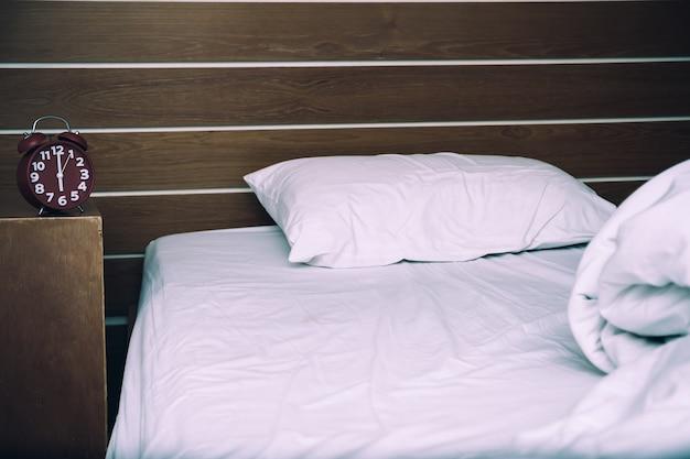 Lit blanc désordonné et un oreiller, mur en bois le matin